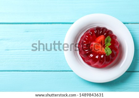 Delicious red jelly with strawberry and mint on light blue wooden table, top view. Space for text Stock photo ©