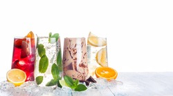 delicious refreshing summer drinks . Sangria , lemonade, iced chocolate drink , a mojito on a white background . Ice cubes around glasses with drinks . Natural collage of beverages. copy space