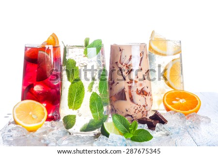 delicious refreshing summer drinks . Sangria , lemonade, iced chocolate drink , a mojito on a white background . Ice cubes around glasses with drinks . Natural collage of beverages