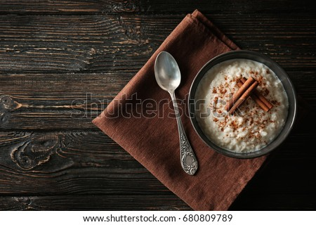 Delicious rice pudding with cinnamon in bowl on wooden background Stock photo ©
