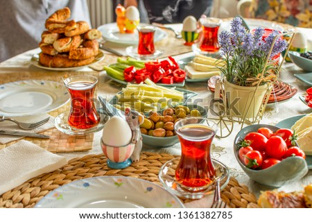 Delicious rich Traditional Turkish breakfast include tomatoes, cucumbers, cheese, butter, eggs, honey, bread, bagels, olives and tea cups. Ramadan Suhoor aka Sahur (morning meal before fasting).  #1361382785
