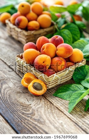 Delicious ripe apricots in a wooden bowl on the table close-up.Healthy fruits. Horizontal top view. Free space for your text. Сток-фото ©