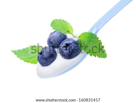Delicious ripe blueberry on white yogurt and  leaves of mint, in  blue spoon