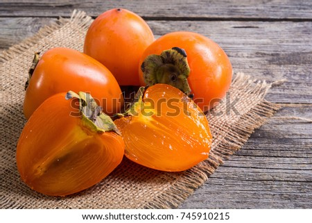 Delicious ripe persimmon fruit on wooden background