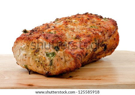 Delicious Roasted Brisket of Pork Baked in Herbs and Spices Full Body closeup on Wood Cutting Board