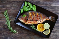 delicious roasted dorado or sea bream fish with lemon and orange slices, spices, fresh rosemary and spinach on black plate on old dark wooden table view from above