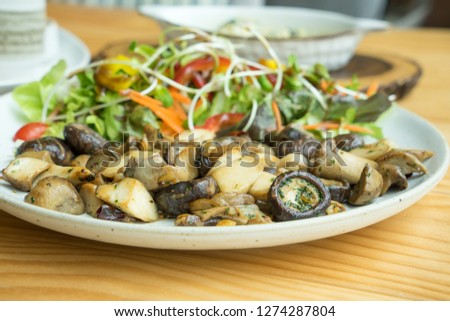 Delicious roasted mix mushroom salad and raw fresh young sunflower seed spout, carrot and various vegetable in white ceramic plate on wooden table.  Healthy food concept.