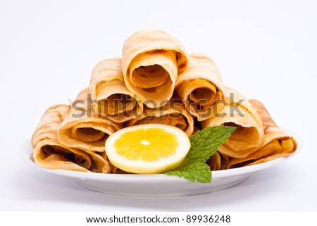 Delicious rolled crepes with lemon and mint, isolated on white background.