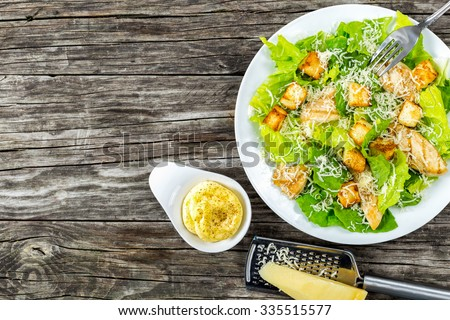 Delicious salad with croutons, grilled chicken breast, grated parmesan cheese and cos lettuce,  with sauce in the gravy boat, simply and healthy recipe, horizontal top view