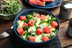 Delicious salad with watermelon served on wooden table