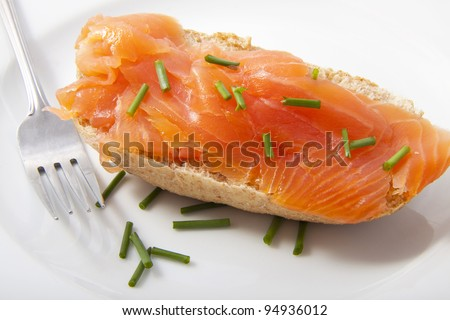 Delicious salmon on bread with a fork on white plate
