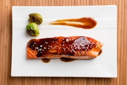 Delicious salmon teriyaki dish top view. Japanese cuisine inspired dinner consisting of a grilled salmon fillet glazed in delicious teriyaki sauce (soy sauce base). Healthy brussel sprouts as sides.