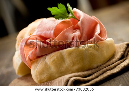 delicious sandwich on wooden table with mortadella sausage