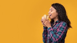 Delicious Sandwich. Side View Portrait Of Happy Black Female Model Eating Burger. African American Lady With Open Mouth Holding And Biting Snack, Orange Studio Background, Banner, Copy Space, Panorama
