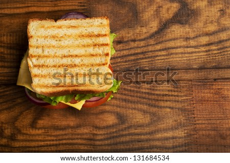 Delicious sandwich stacked high with a juicy ham , cheese, fresh lettuce, onion and tomato on a fresh bun with  standing on  wooden table