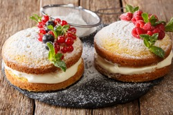 Delicious sandwich Victoria cake with black and red currants, raspberries and mint closeup on the table. horizontal
