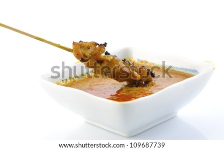 Delicious Satay chicken and peanut sauce over white background