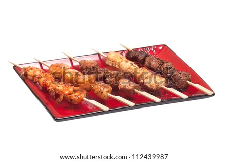 Delicious satay collection on a red plate with different meat