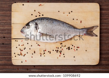 Delicious seafood concept in brown. Sea bream  on wooden chopping board with colorful peppercorns.