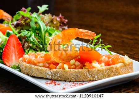 Delicious seafood dish. Bread with tomatoes and shrimps and basil leaves in white plate, close-up