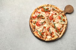 Delicious seafood pizza on light grey table, top view. Space for text