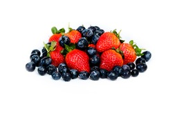 Delicious seasonal fruits, Blueberries and Strawberries, mixed together on a white top against a white background. A perfect healthy breakfast or snack, vegan, and full of vitamins. Spring or Summer.