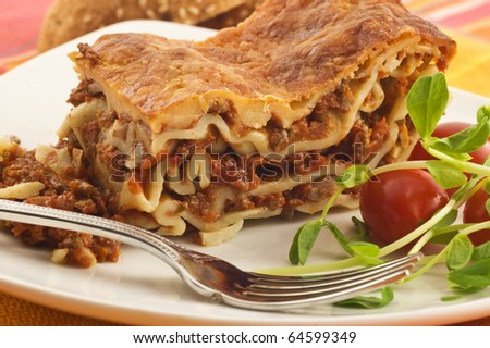 Delicious slice of meat lasagna with grape tomatoes and pea shoots on white plate
