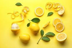 Delicious sliced and peeled lemons with green leaves on color background