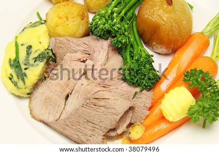 Delicious sliced roast lamb with baked vegetables.