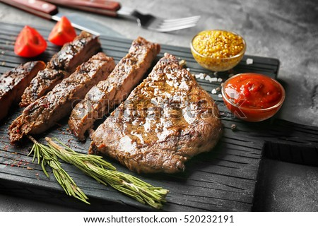 Delicious sliced steak with spices on board and grey table