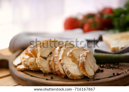 Delicious sliced turkey breast on wooden board