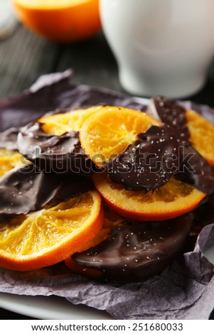 Delicious slices of orange coated chocolate on plate on black wooden background