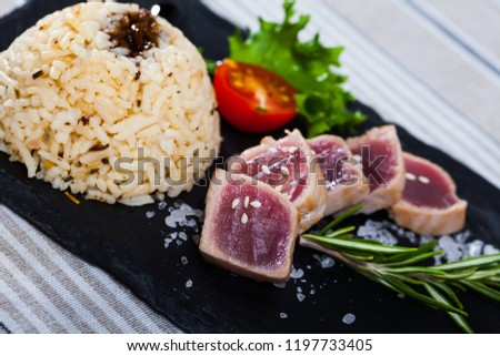 Delicious slightly fried tuna (tataki) served with spicy rice and citrus base soy sauce on black serving board #1197733405