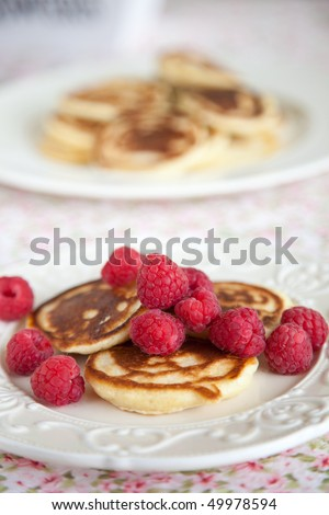 Delicious small pancakes with raspberries on a small plate