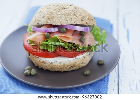 Delicious smoked salmon burger with lettuce, onions, tomato, capers and cream cheese