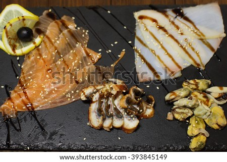 Delicious smoked salmon fish platter garnished with lemon and red caviar. Isolated on a white background.