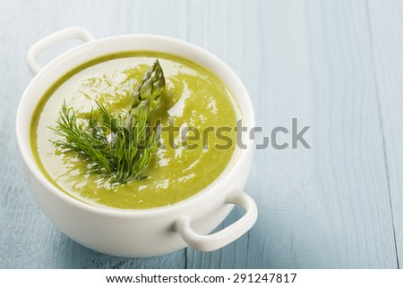 Delicious soup with asparagus, served in white bowls. Stock photo ©