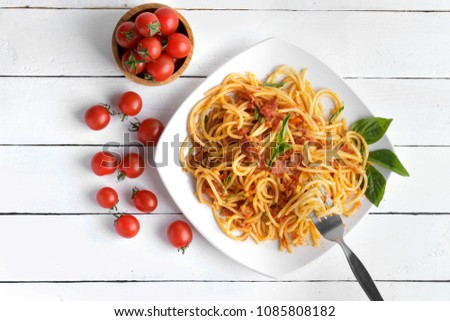 Delicious  spaghetti amatriciana sauceon a light concrete and tomato sauce on white plate
