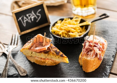 Delicious spanish tapas and beer served on a wooden table. Foto stock ©