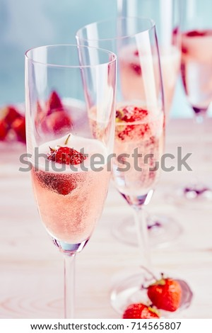 Delicious sparkling pink champagne with fresh strawberries served in stylish flutes for a romantic celebration or special occasion #714565807