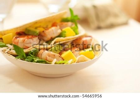 Delicious Spicy shrimp taco with lettuce jimaca salad mango and avocado