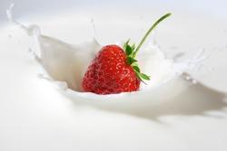 Delicious strawberry splashing into milk