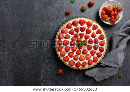 Delicious strawberry tart with whipped cream and mascarpone, on a dark concrete background. Top view. Copy space.