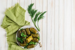 Delicious stuffed grape leaves (traditional doom Mediterranean cuisine Dolma) on a black plate with fresh cilantro and dill on a light wooden background top view with copyspace