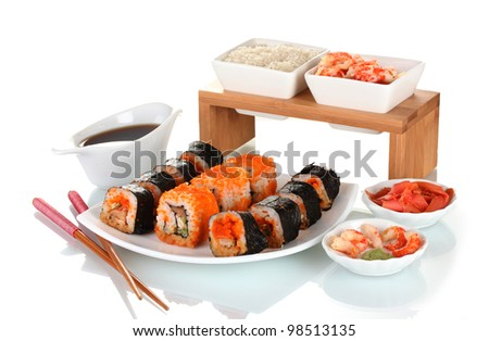 delicious sushi on plate, chopsticks, soy sauce, fish and shrimps isolated on white