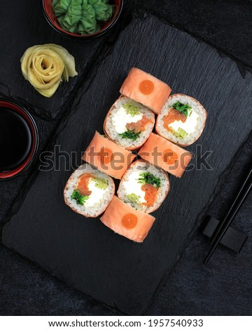 Delicious sushi rolls. Close-up of rolling sushi. making sushi with sauce and sesame seeds, we pour delicious fresh rolls with sauce. Dark background. Beautiful photo of sushi rolls. Top view.