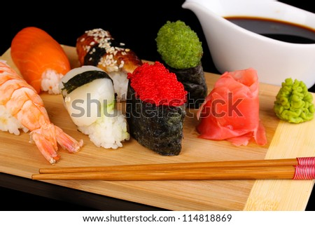 delicious sushi served on wooden board close-up