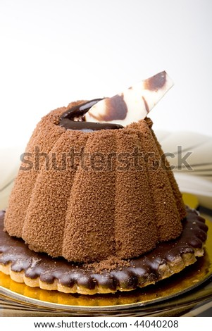 Delicious sweet chocolate mousse cake pastry on top of a glazed cookie dessert