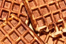 Delicious sweet food. Close up shot of freshly baked Belgian waffles, traditional Belgian dessert. Sweet food, unhealthy eating