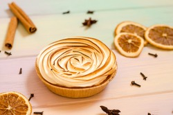 Delicious sweet orange tart with a baked top, and a rainbow background with spices, cinnamon, star anise, cloves, as a background for holiday menus and posts